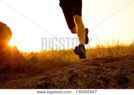 Close-up of Sportsman's Legs Running on the Rocky Mountain Trail at Sunset. Active Lifestyle Concept