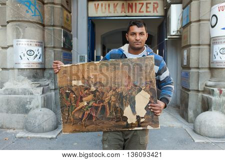 ZAGREB, CROATIA - OCTOBER 17, 2013: Roma man holding ruined painting collected from the street garbage dump.