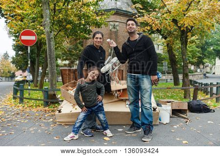ZAGREB, CROATIA - OCTOBER 14, 2013: Roma family fooling around for camera at garbage dump.