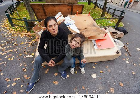 ZAGREB, CROATIA - OCTOBER 14, 2013: Roma mother and daughter sitting at the garbage dump.