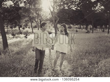 young happy beautiful couple in love walking together on grass and trees park romantic landscape on sunset in summer with woman having pregnant belly in romance and family concept in black and white