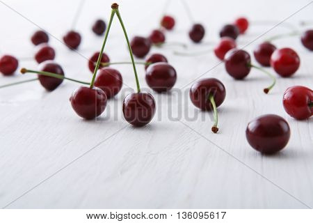 Sweet fresh cherries background, Scattered fruits closeup on white rustic wood, pattern with copy space.