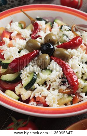 Shopska salad with cheese, hot peppers, olives, cucumber, tomato and onion