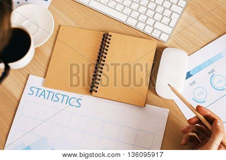 Top view of man drinking coffee and doing paperwork on wooden office desktop with blank brown notepad business report and keyboard. Mock up