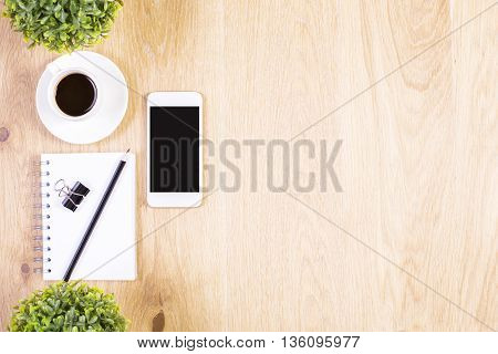 Top view of wooden desktop with blank smart phone pencil and peg on spiral notepad coffee cup and two plants. Mock up