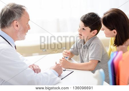How are you feeling today. Little boy telling to pediatrician something, holding pills in his hands