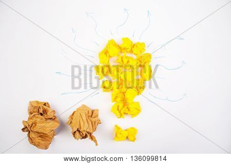 Idea concept with yellow paper bulb and arrow doodles on white background