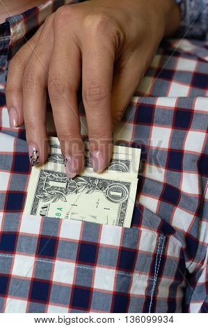 Dollars in the shirt pocket and woman's hand
