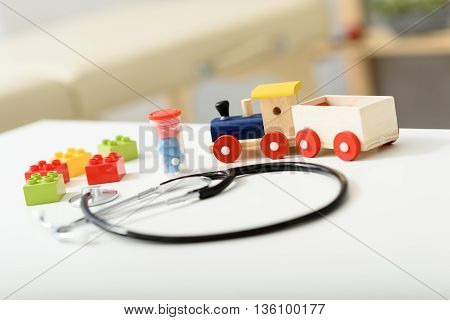 Welcome to toy clinic. Close up of wooden toy and pills with stethoscope device on top of white table
