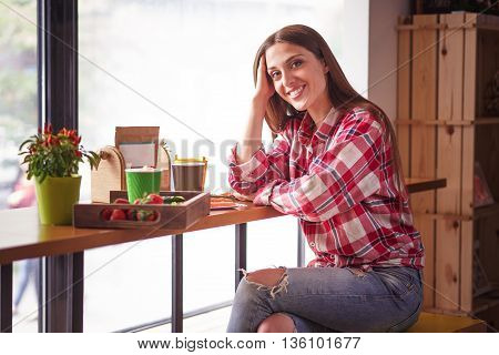 Toned image of beautiful female sitting at table and looking at camera. Blond lady eating sandwich and drinking cup of coffee in cafe or restaurant.