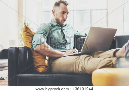 Bearded Hipster working Laptop modern Interior Design Loft Office.Man work Vintage Sofa, Use contemporary Notebook, typing keyboard.Blurred Background.Creative Business Startup Idea.Horizontal, Film