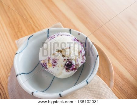 Strawberry ice cream in bowl on wood table
