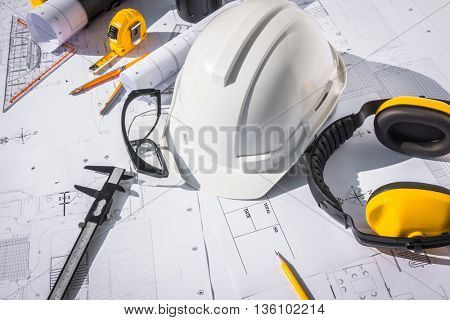Construction plans with White helmet and drawing tools on blueprints