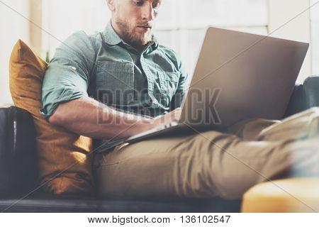 Bearded Hipster working Laptop modern Interior Design Loft Office.Man work Vintage Sofa, Use contemporary Notebook, Browsing Internet.Blurred Background.Creative Business Startup Idea.Horizontal, Film
