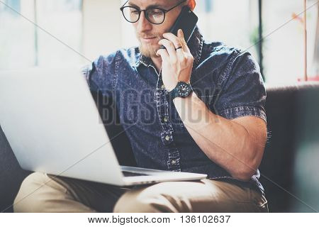 Muscular Bearded Man working Laptop modern Interior Design Loft Office, Sitting Vintage Sofa.Using contemporary Smartphone Hand.Blurred Background.Creative Business Startup Process Idea.Horizontal, Film