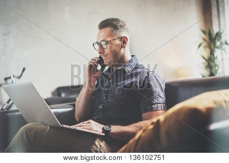 Successful Businessman working Laptop modern Interior Design Loft Office.Man work Vintage Sofa, Using contemporary Smartphone Hand Calling.Blurred Background.Business Startup Idea Process.Film effect