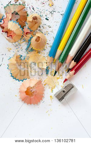 sharpener colored wooden pencils and pencil shavings on white