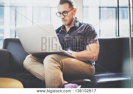 Bearded Trader working Laptop modern Interior Design Loft Office.Handsome Man work Vintage Sofa.Use contemporary Notebook, Browsing Internet.Blurred Background.Business Startup Idea Process.Film effect