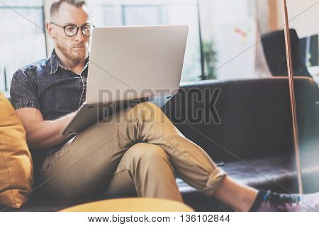 Bearded Hipster working Laptop modern Interior Design Loft Office.Guy work Vintage Sofa, Use contemporary Notebook, Browsing Internet.Blurred Background.Creative Business Startup Idea.Horizontal, Film