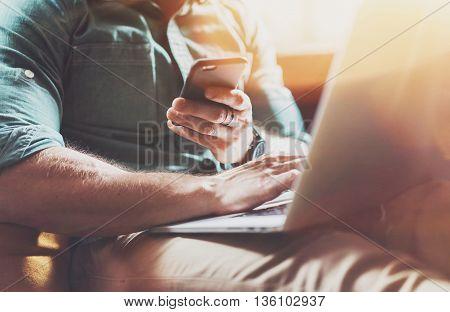 Successful Risk Manager working Laptop modern Interior Design Loft Office.Men work Vintage Sofa, Using contemporary Smartphone Hand Calling.Blurred Background.Business Startup Idea Process.Film Effect