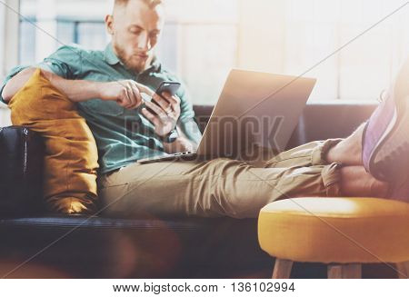 Bearded Hipster working Laptop modern Design Interior Studio Loft.Men work Vintage Sofa, Use Contemporary Notebook, Touching Smartphone.Blurred Background.Creative Business Startup Idea.Film flare