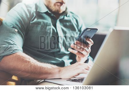 Bearded Businessman work Laptop modern Design Interior Loft Studio.Men Lounge Vintage Sofa.Use contemporary Notebook Send Message Smartphone.Blurred background.Creative Process Startup Idea.Film