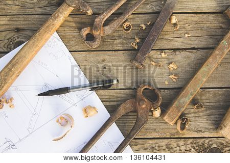 A sketch of some construction, pencil and old rusty tools on wooden table