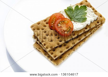 Healthy low carb breakfast snack on white dish crispbread and fresh tomato on cream cheese with parsley and pepper