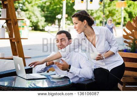 man and woman working on laptop at outdoors cafe during the break.