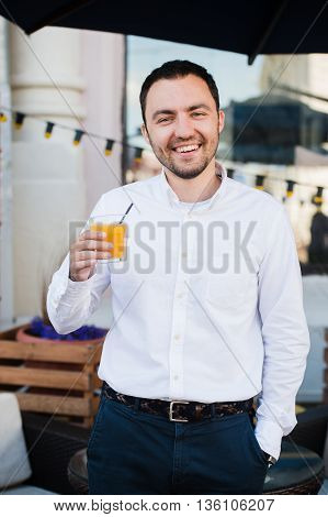 Young Man Holding Glass Of Orange Juice, Outdoors.