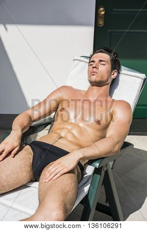 Shirtless Young Man Drying Off in Hot Sun, Muscular Man Wearing Bathing Suit Sunbathing on Beach Lounge Chair, Eyes Closed