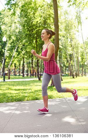 Slender fit young woman in skin-tight sportswear is jogging on the park alley
