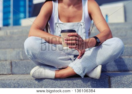 Close-up of stylish female in overalls who is sitting with her legs crossed and holding a cup of coffee