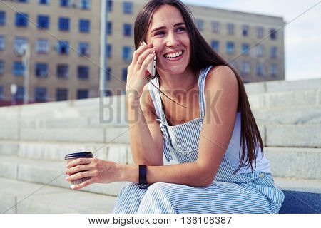 Young beautiful woman decided to sit for a while and chat on the phone during her coffee break