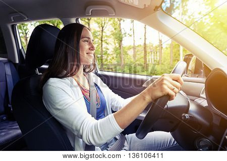 Young beautiful confident smiling woman is driving on a sunny day with her seat belt fastened