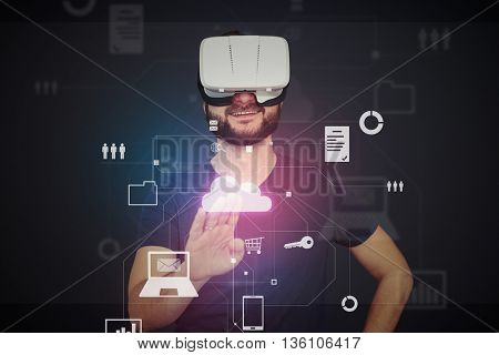 Young man in VR-headset is pressing a cloud icon on virtual interactive touch screen over dark background