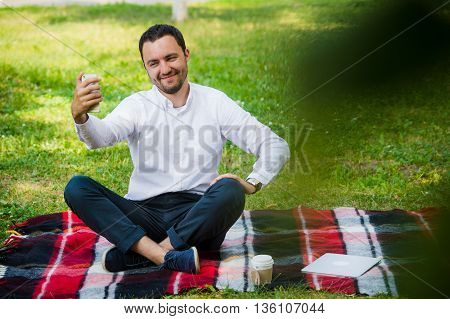 Photo of handsome nice guy outdoors at morning. Young man smiling and making selfie photo on mobile phone with cool expressions.