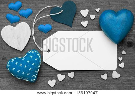 Label With Blue Textile Hearts On Wooden Gray Background. Copy Space For Advertisement Or Your Free Text Here. Retro Or Vintage Style. Black And White Image With Colored Hot Spot.