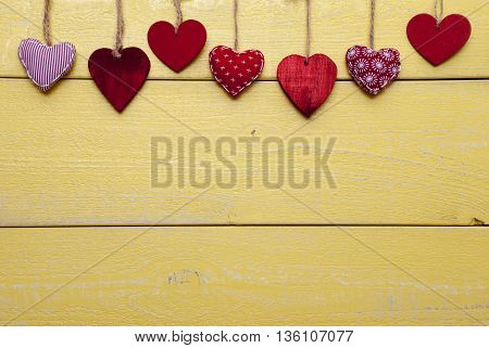 Wooden Background With Red And Yellow Hearts Hanging In A Row. Copy Space For Advertisement Or Free Text.  Loving Greeting Card For Valentines Or Mothers Day
