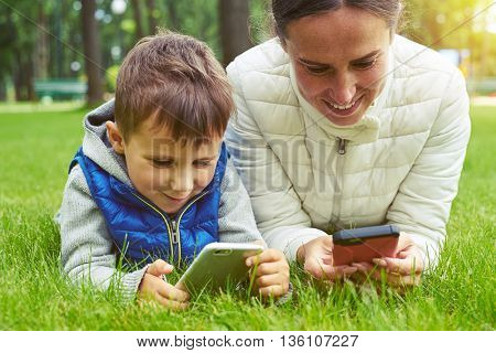 Mother and her small son are enjoying a nice day in park lying on green grass and playing on their smart devices