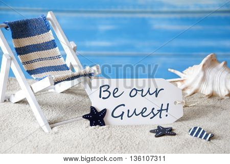Summer Label With English Text Be Our Guest. Blue Wooden Background. Card With Holiday Greetings. Beach Vacation Symbolized By Sand, Deck Chair And Shell.