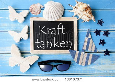 Flat Lay Of Chalkboard On Blue Wooden Background. Nautical Summer Decoration As Holiday Greeting Card. German Text Kraft Tanken Means Relax