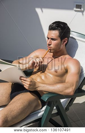 Topless handsome man in underwear on deckchair looking pensively away with pencil and notebook