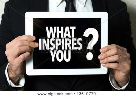 Business man holding a tablet with the text: What Inspires You?