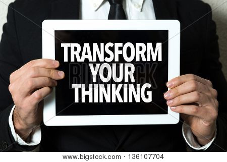 Business man holding a tablet with the text: Transform Your Thinking