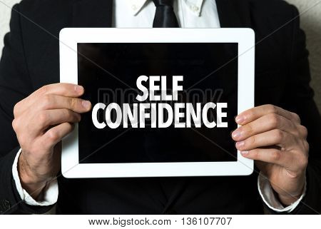 Business man holding a tablet with the text: Self Confidence