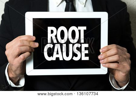 Business man holding a tablet with the text: Root Cause