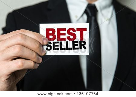 Business man holding a card with the text: Best Seller