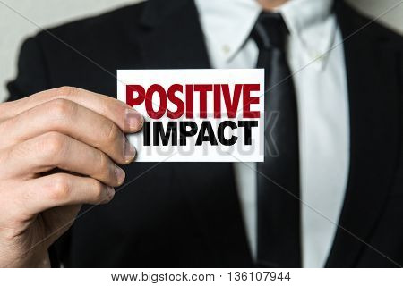 Business man holding a card with the text: Positive Impact