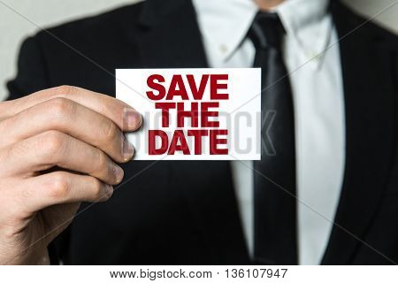 Business man holding a card with the text: Save the Date